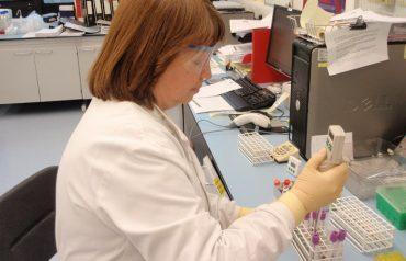 Lab technician filling test tubes